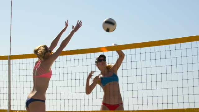 vídeos de stock e filmes b-roll de women players play beach volleyball and a player hitting spiking the ball. - óculos de sol