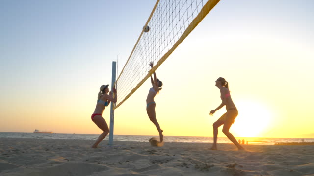 women players play beach volleyball and a player hitting spiking the ball. - slow motion - volleyballnetz stock-videos und b-roll-filmmaterial