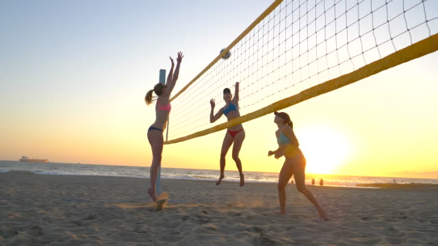 women players play beach volleyball and a player hitting spiking the ball. - slow motion - bikini bottom stock videos & royalty-free footage