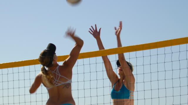 vídeos de stock e filmes b-roll de women players play beach volleyball and a player hitting spiking the ball. - slow motion - óculos de sol