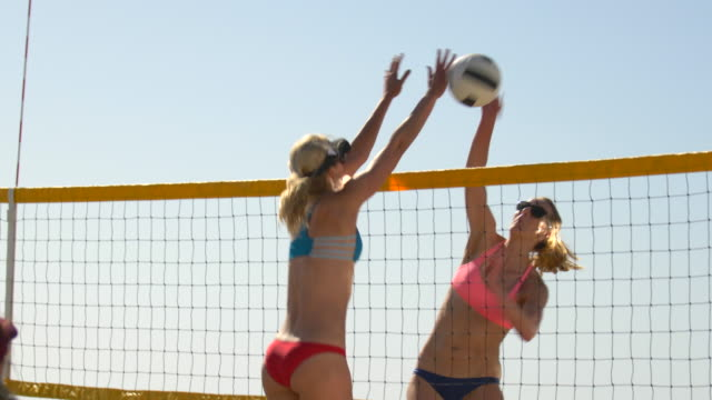 women players play beach volleyball and a player hitting spiking the ball. - slow motion - volleyball stock-videos und b-roll-filmmaterial