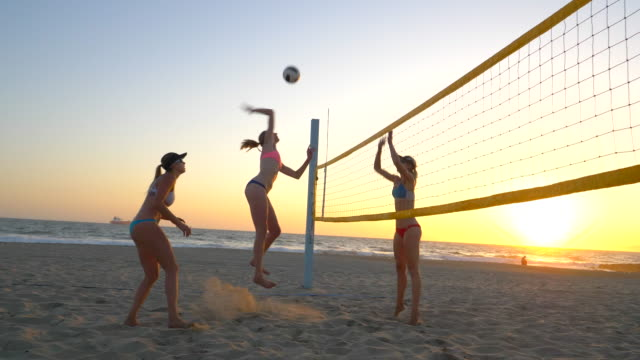 vídeos de stock, filmes e b-roll de women players play beach volleyball and a player hitting spiking the ball. - slow motion - atividade