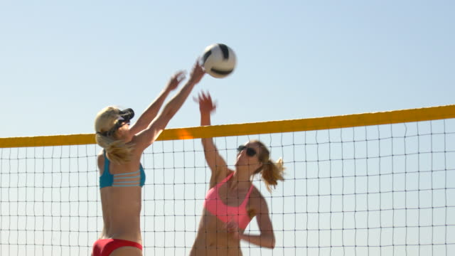 women players play beach volleyball and a player hitting spiking the ball. - slow motion - sonnenschild stock-videos und b-roll-filmmaterial
