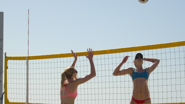 women players play beach volleyball and a player hitting spiking the ball. - slow motion - filmed at 180 fps - sonnenschild stock-videos und b-roll-filmmaterial