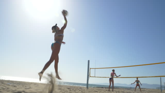women players play beach volleyball and a player jump serves an ace serve. - volleyballnetz stock-videos und b-roll-filmmaterial