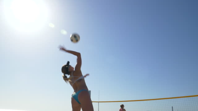 women players play beach volleyball and a player jump serves an ace serve. - badebekleidung stock-videos und b-roll-filmmaterial