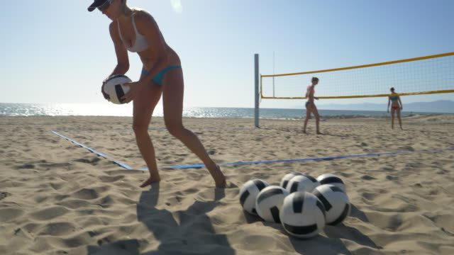 Women players play beach volleyball and a player jump serves an ace serve.