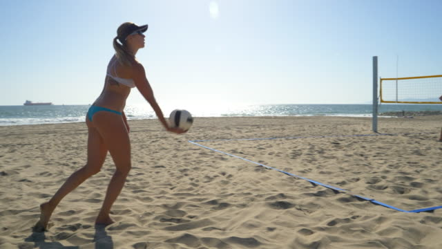 women players play beach volleyball and a player jump serves an ace serve. - slow motion - beach volleyball stock videos & royalty-free footage