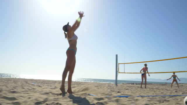 women players play beach volleyball and a player jump serves an ace serve. - slow motion - volleyballnetz stock-videos und b-roll-filmmaterial