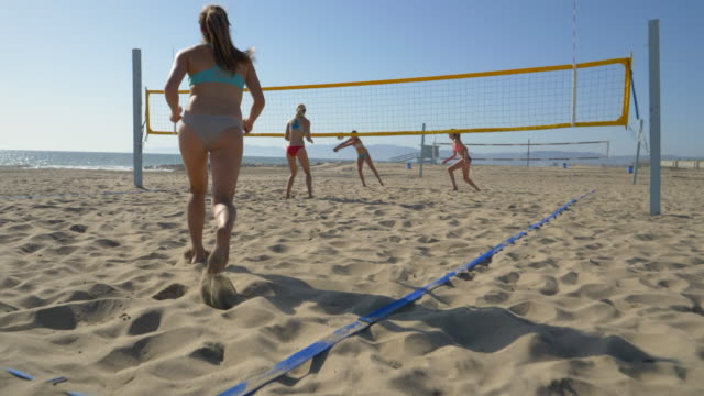 women players play beach volleyball and a player jump serves serving the ball. - 4人点の映像素材/bロール