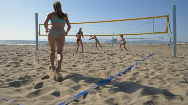 vidéos et rushes de women players play beach volleyball and a player jump serves serving the ball. - quatre personnes