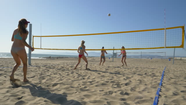 Women players play beach volleyball and a player jump serves serving the ball.