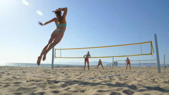 women players play beach volleyball and a player jump serves serving the ball. - slow motion - wettbewerb konzepte stock-videos und b-roll-filmmaterial