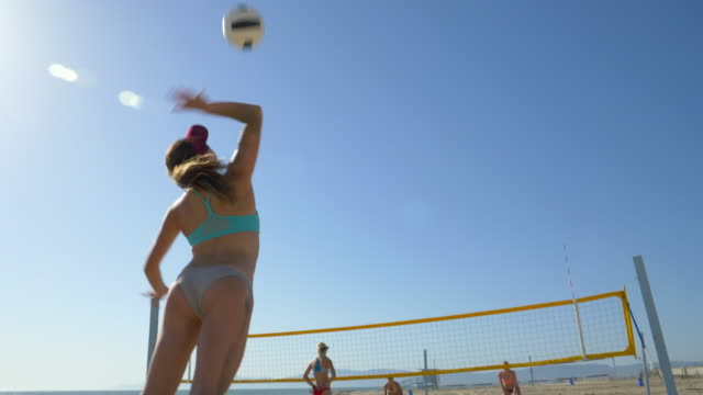 women players play beach volleyball and a player jump serves serving the ball. - slow motion - sonnenschild stock-videos und b-roll-filmmaterial