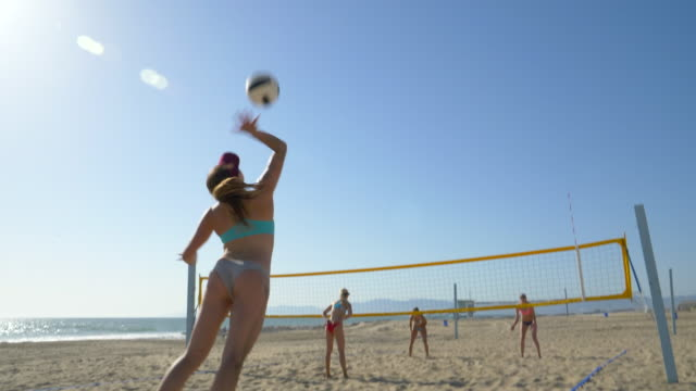 women players play beach volleyball and a player jump serves serving the ball. - slow motion - beach volleyball stock videos & royalty-free footage