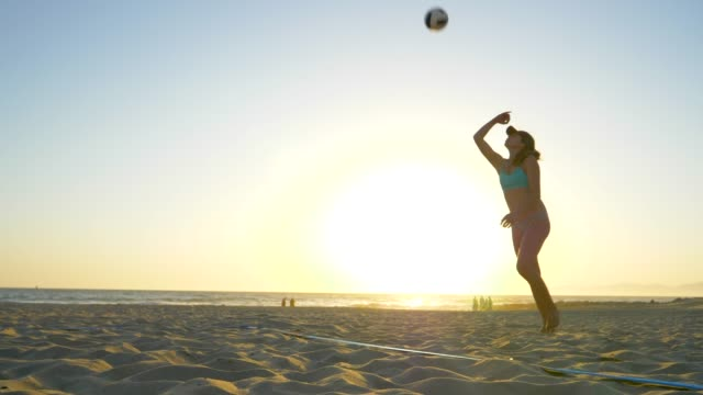 women players play beach volleyball and a player jump serves serving the ball. - slow motion - ショットを決める点の映像素材/bロール
