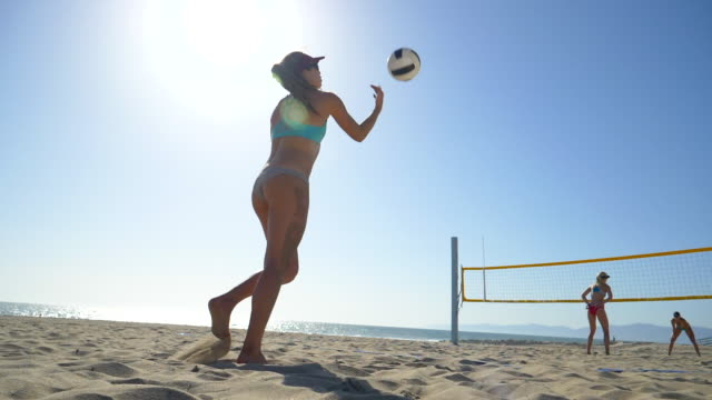 Women players play beach volleyball and a player jump serves serving the ball. - Slow Motion - filmed at 180 fps
