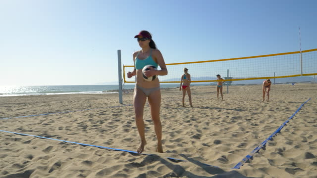 women players play beach volleyball and a player serves the ball. - slow motion - sonnenschild stock-videos und b-roll-filmmaterial