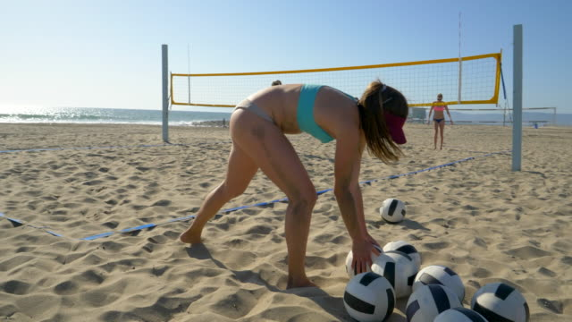 women players play beach volleyball and a player serves the ball. - slow motion - bikini bottom stock videos & royalty-free footage