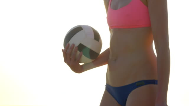 women players play beach volleyball and a player serves the ball. - slow motion - volleyball sport stock videos and b-roll footage