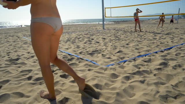 women players play beach volleyball and a player serves the ball. - slow motion - filmed at 180 fps - sonnenschild stock-videos und b-roll-filmmaterial