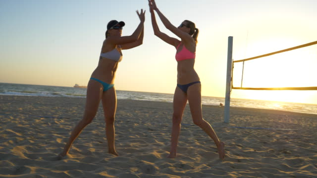 women players play beach volleyball and celebrate a point won. - slow motion - volleyball sport stock videos and b-roll footage