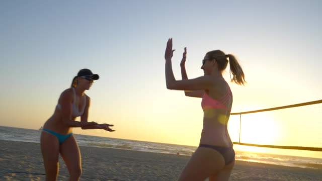 women players play beach volleyball and celebrate a point won. - slow motion - sonnenschild stock-videos und b-roll-filmmaterial
