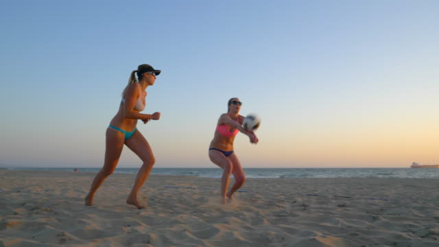 Women players play beach volleyball at sunset and a player hand sets the ball.