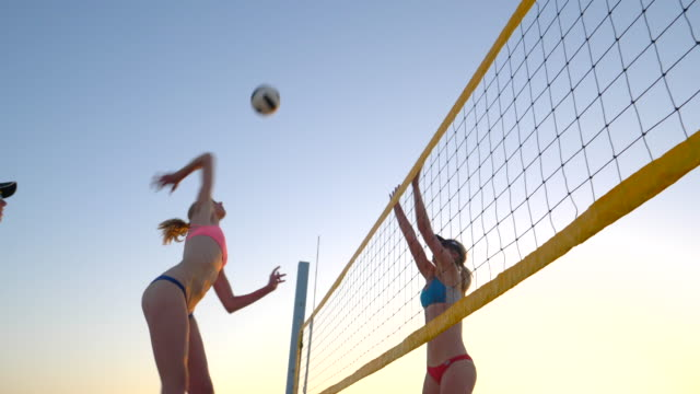 women players play beach volleyball at sunset and a player hand sets the ball. - slow motion - volleyballnetz stock-videos und b-roll-filmmaterial