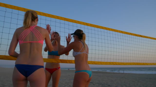 Women players play beach volleyball one team congratulates the other.