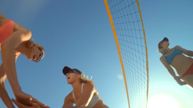 pov of women players playing beach volleyball and a girl celebrating a point won. - slow motion - dekolleté stock-videos und b-roll-filmmaterial