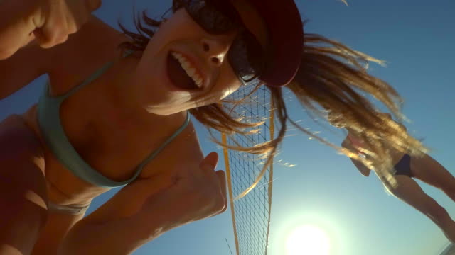 pov of women players playing beach volleyball and a girl celebrating a point won. - slow motion - volleyballnetz stock-videos und b-roll-filmmaterial
