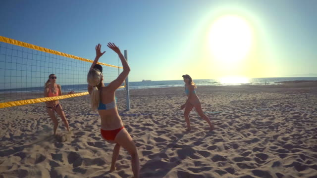 pov of women players playing beach volleyball and a girl hitting the ball. - slow motion - sun visor stock videos & royalty-free footage