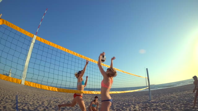 pov of women players playing beach volleyball and jousting at the net. - slow motion - volleyball net stock videos & royalty-free footage