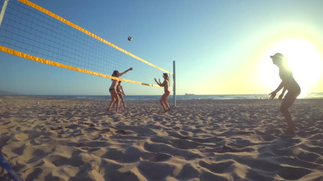 pov of women players playing beach volleyball with a girl diving to dig a ball. - slow motion - volleyballnetz stock-videos und b-roll-filmmaterial