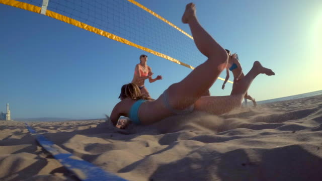 pov of women players playing beach volleyball with a girl diving to dig a ball. - volleyballnetz stock-videos und b-roll-filmmaterial