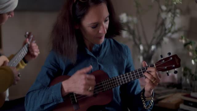 Women playing ukulele
