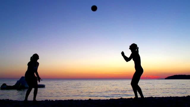 hd: frauen spielen volleyball bei sonnenuntergang - volleyball spielball stock-videos und b-roll-filmmaterial