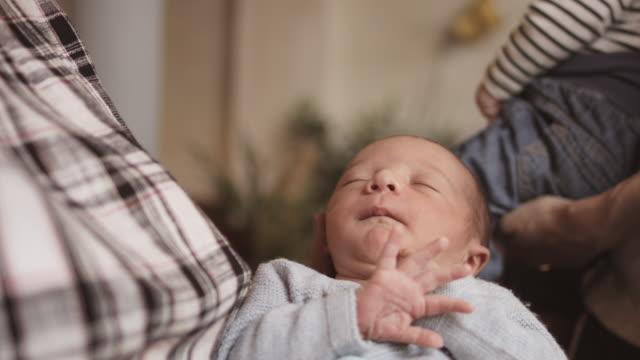 vídeos de stock e filmes b-roll de women playing with sleeping baby in restaurant - vida de bebé