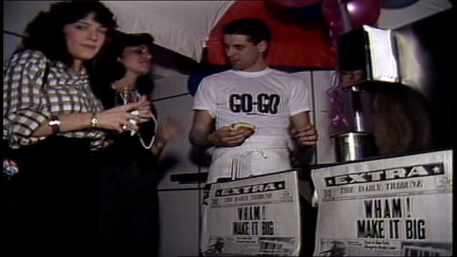 vídeos y material grabado en eventos de stock de women pointing to newpaper at hot dog cart that say wham makes it big - música pop