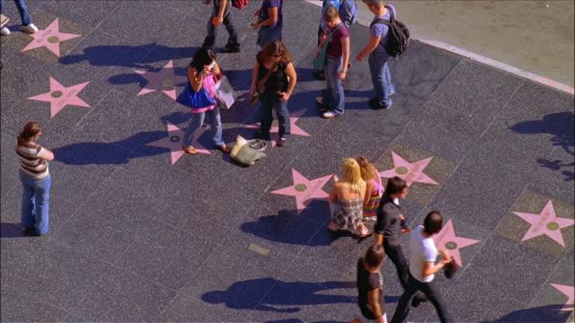stockvideo's en b-roll-footage met women posing for portrait next to stars on hollywood walk of fame / people walking past on sidewalk / hollywood, los angeles, california - hollywood walk of fame