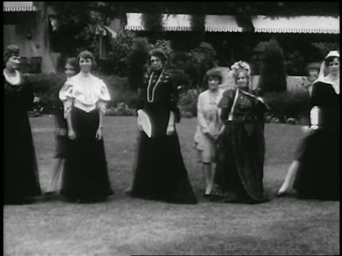 B/W 1929 women posing in 19th C. dress as group of flappers pose by them / Pasadena / newsreel