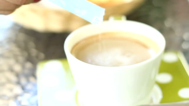 women pouring sugar into a cup of coffee - sprinkles stock videos and b-roll footage