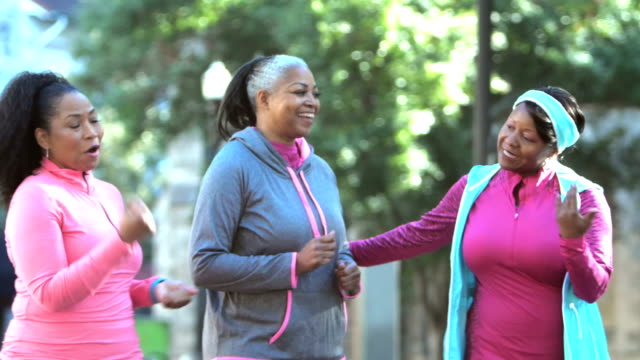 women power walking in the city, talking and smiling - overweight active stock videos & royalty-free footage