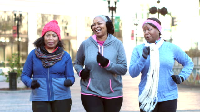 Women power walking, talking, smiling in warm clothing