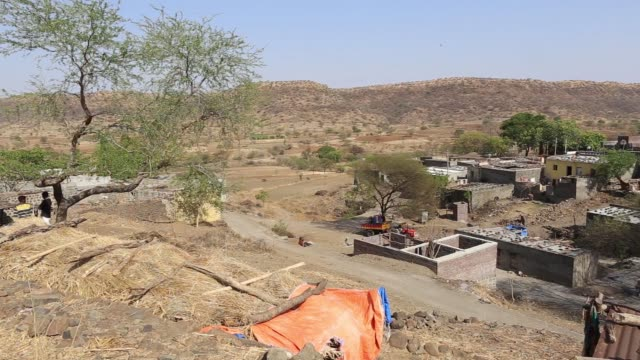 women prepare to fill vessels with water from public drums at a village in beed district maharashtra india on friday april 15 a dried river sits near... - maharashtra stock-videos und b-roll-filmmaterial
