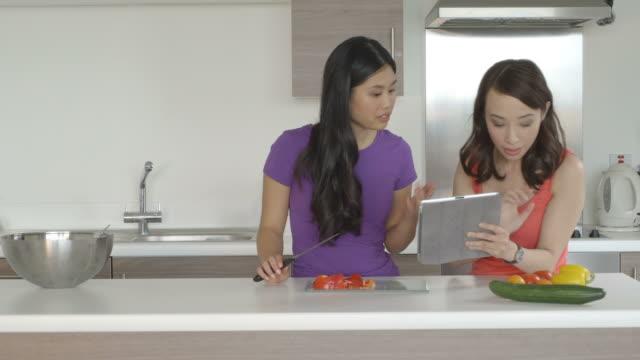 vídeos y material grabado en eventos de stock de women preparing food and using tablet - utensilio para cocinar