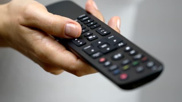 チャンネルを変更するには、リモートコントロールボタンを押す女性 - ラジコン点の映像素材/bロール
