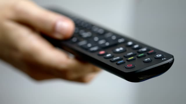 women pressing remote control button to change channels - remote control stock videos & royalty-free footage