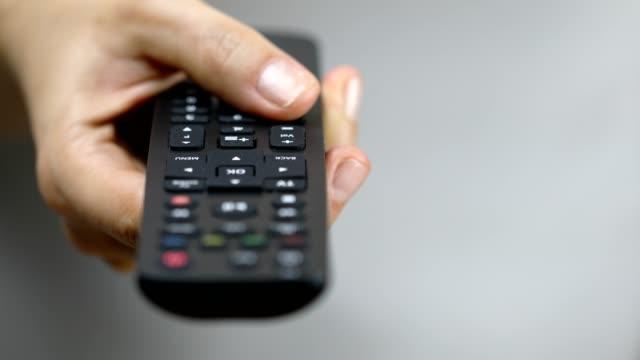 donne che premono il pulsante di controllo remoto per ridurre il volume - remote control video stock e b–roll